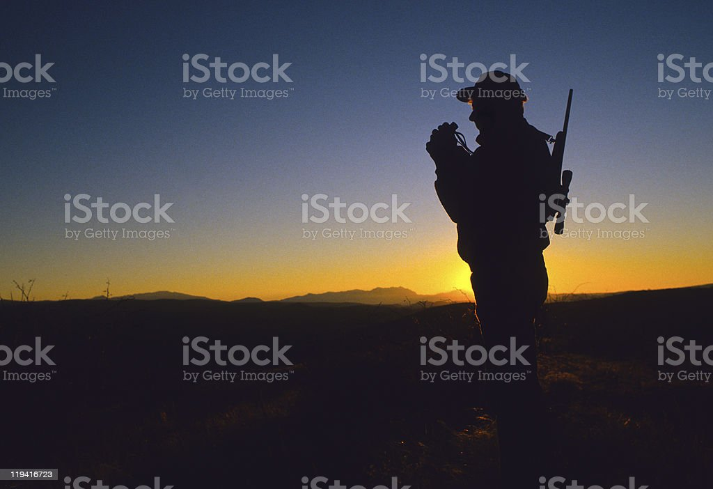 Silhouette of Hunter Glassing stock photo