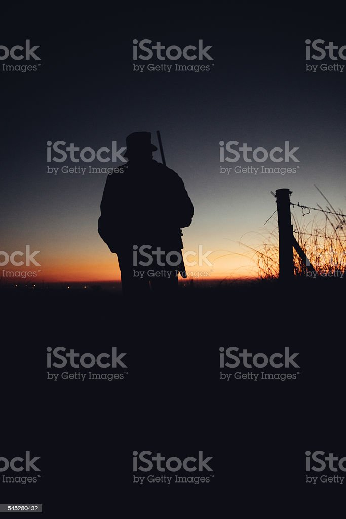Silhouette of hunter with gun at sunrise stock photo