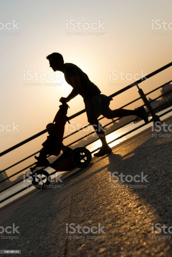 Silhouette of Jogging Father Pushing Stroller on Riverfront stock photo