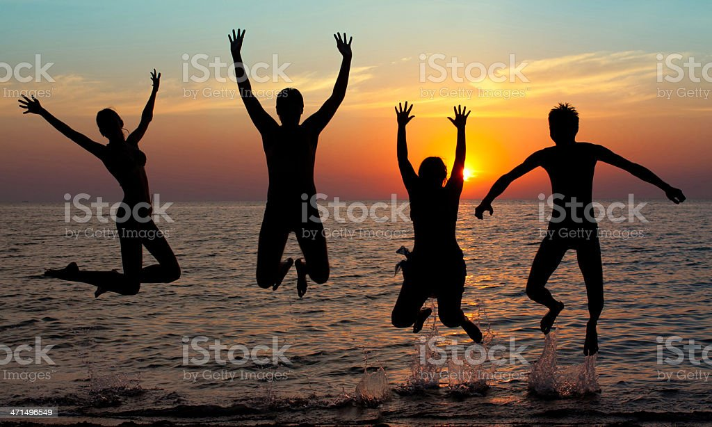 silhouette of jumping people on sunset background royalty-free stock photo