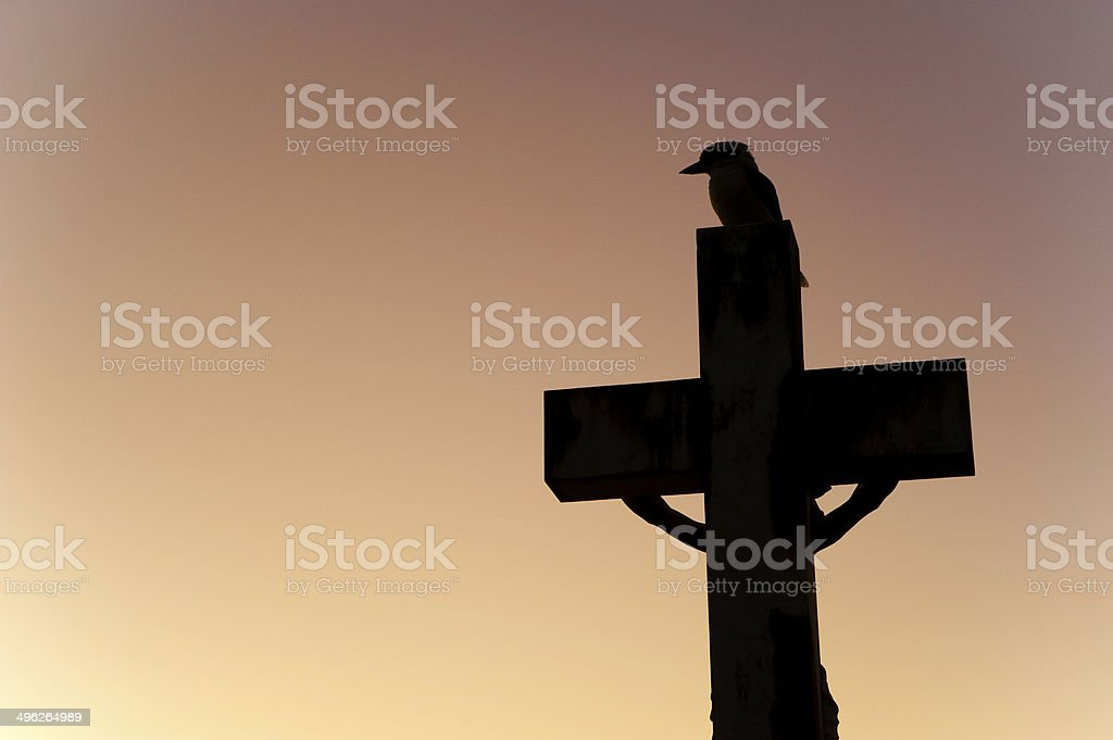 Silhouette of kookaburra on cross stock photo