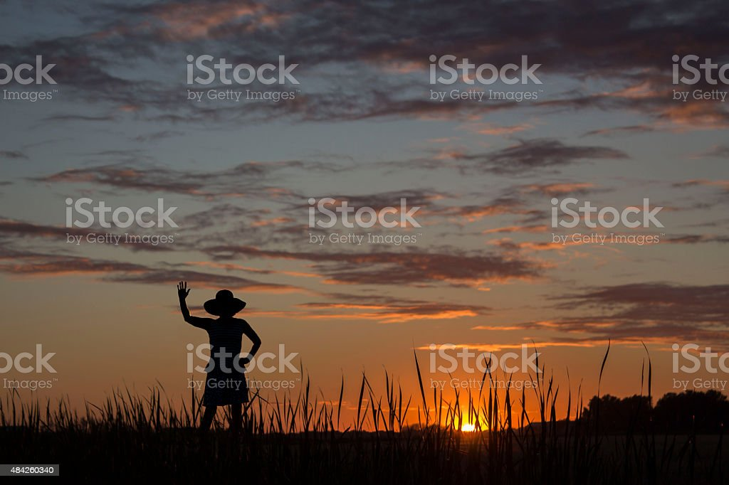 silhouette of lady waving to the setting sun at twilight. stock photo