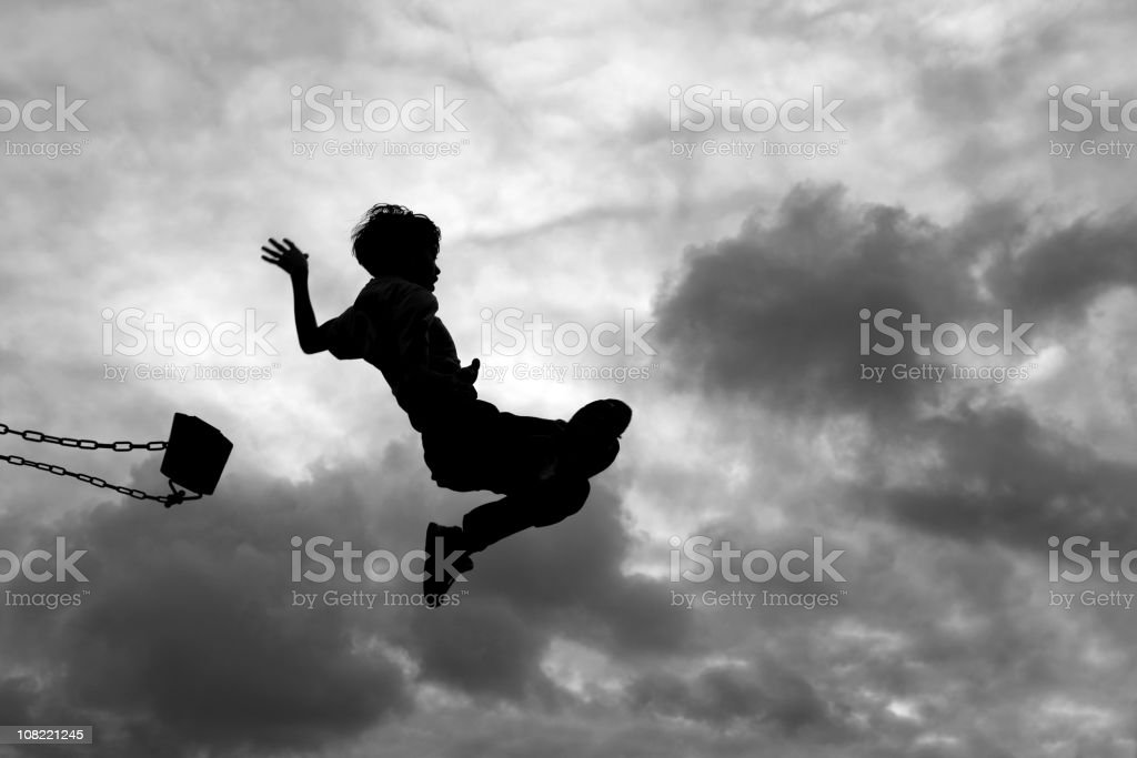 Silhouette of Little Boy Jumping Off Swing stock photo
