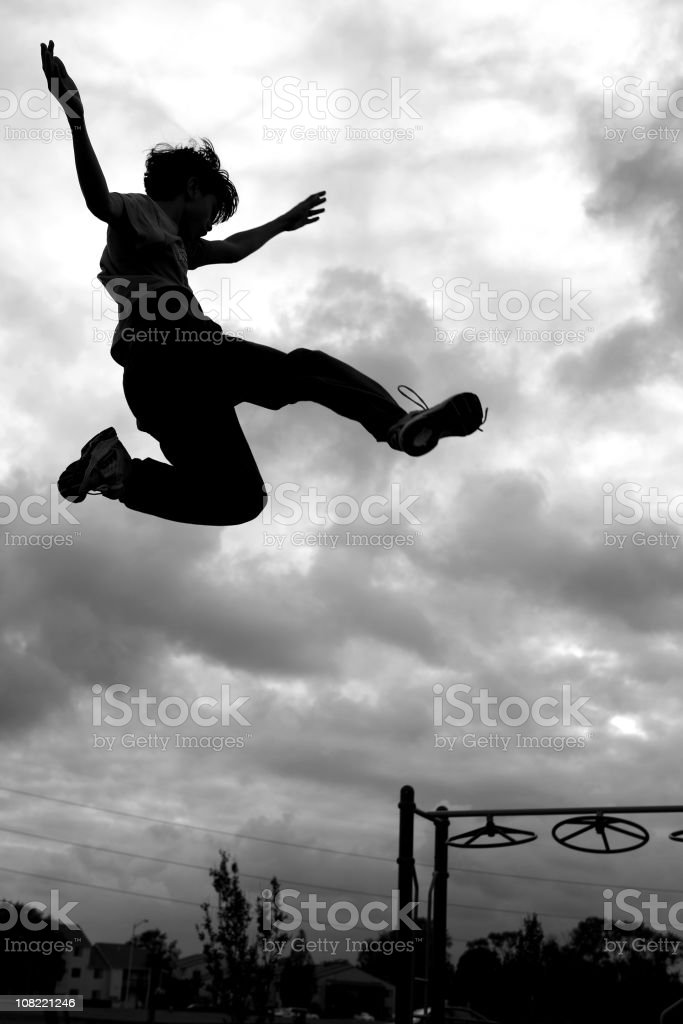 Silhouette of Little Boy Jumping with Playground in Background royalty-free stock photo
