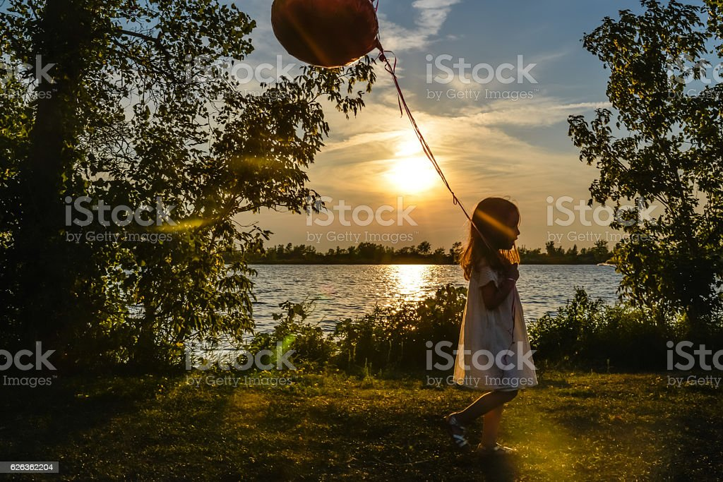Silhouette of little girl playing with balloons at river stock photo