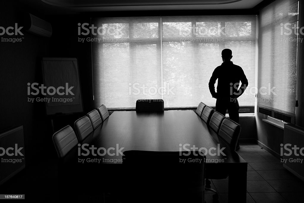 Silhouette Of Lonely Businessman Standing By Boardroom Table In Office royalty-free stock photo