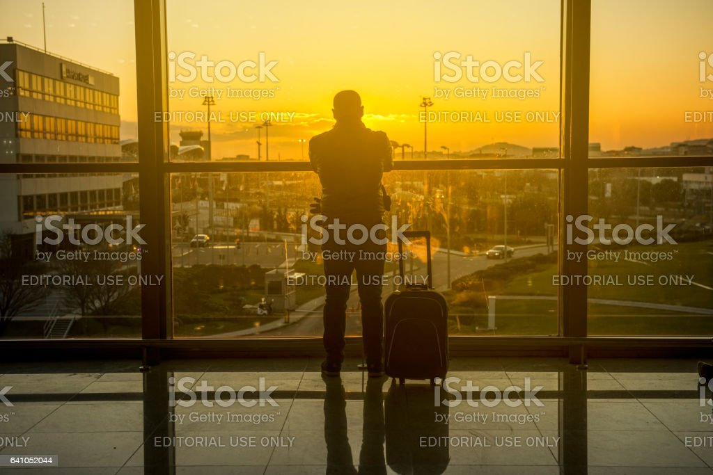 Silhouette of lonely man looking away in airport stock photo