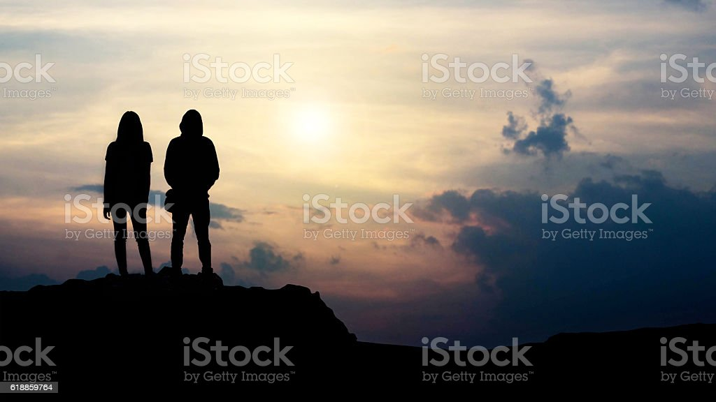 silhouette of love guy and girl against sunset stock photo