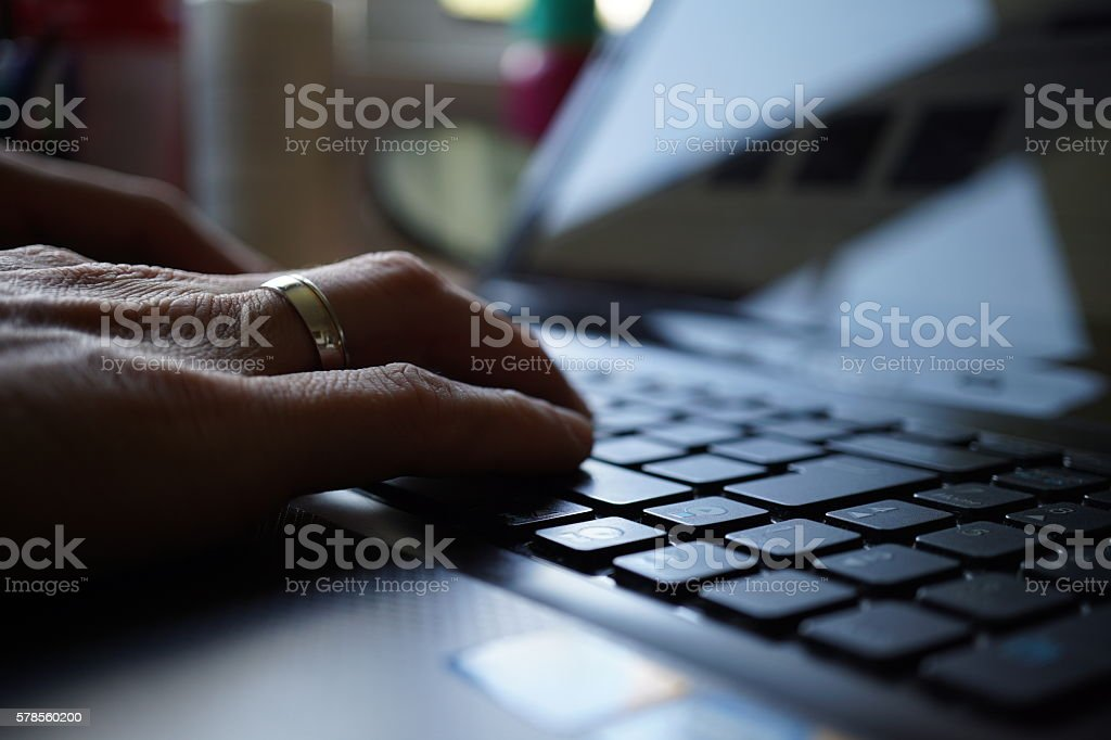 Silhouette of male hand pressing laptop keys stock photo