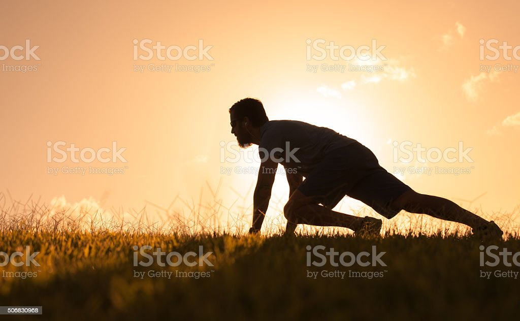 Silhouette of male runner at start. stock photo
