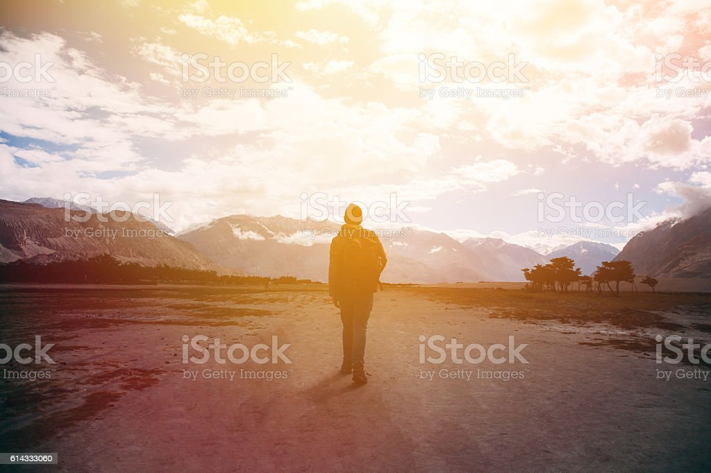 Silhouette of male traveler with backpack walking away stock photo