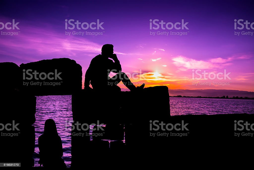 Silhouette of man and girl sitting at sunset stock photo