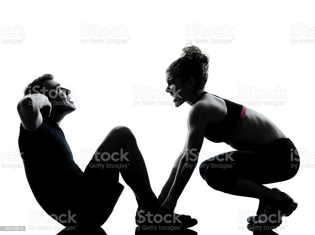 Silhouette of man and woman exercising royalty-free stock photo