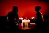 Silhouette of Man and Woman Sitting by Various Candles