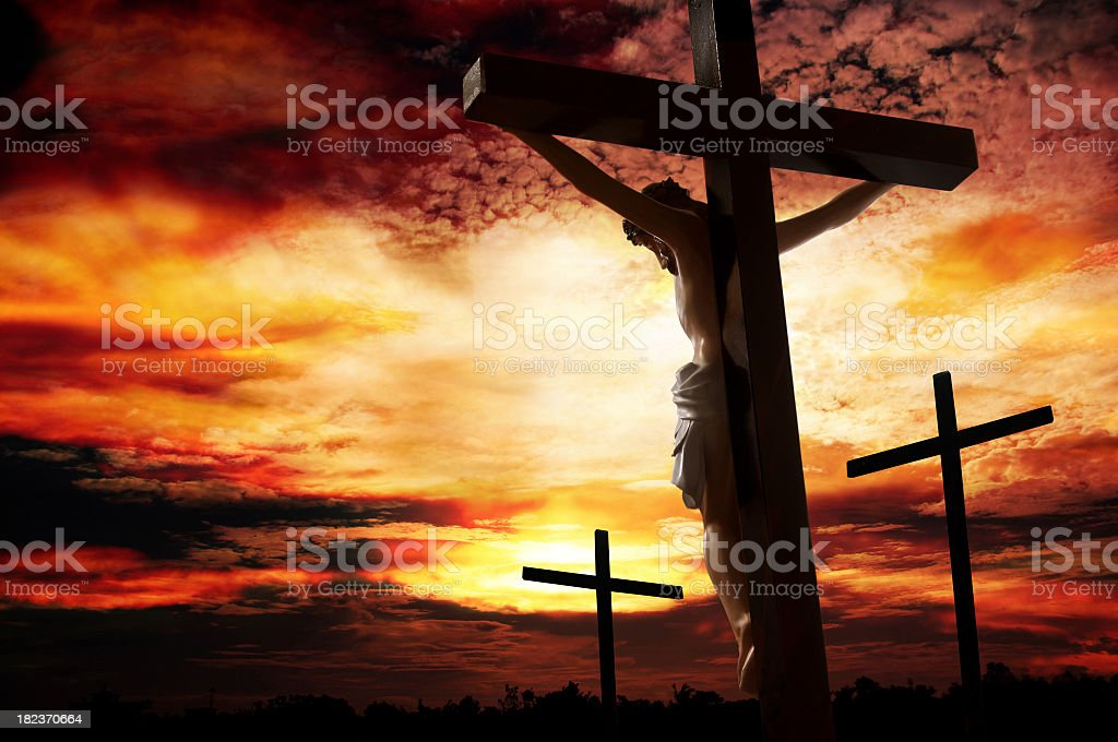 Silhouette of man being crucified against a vivid sunset stock photo