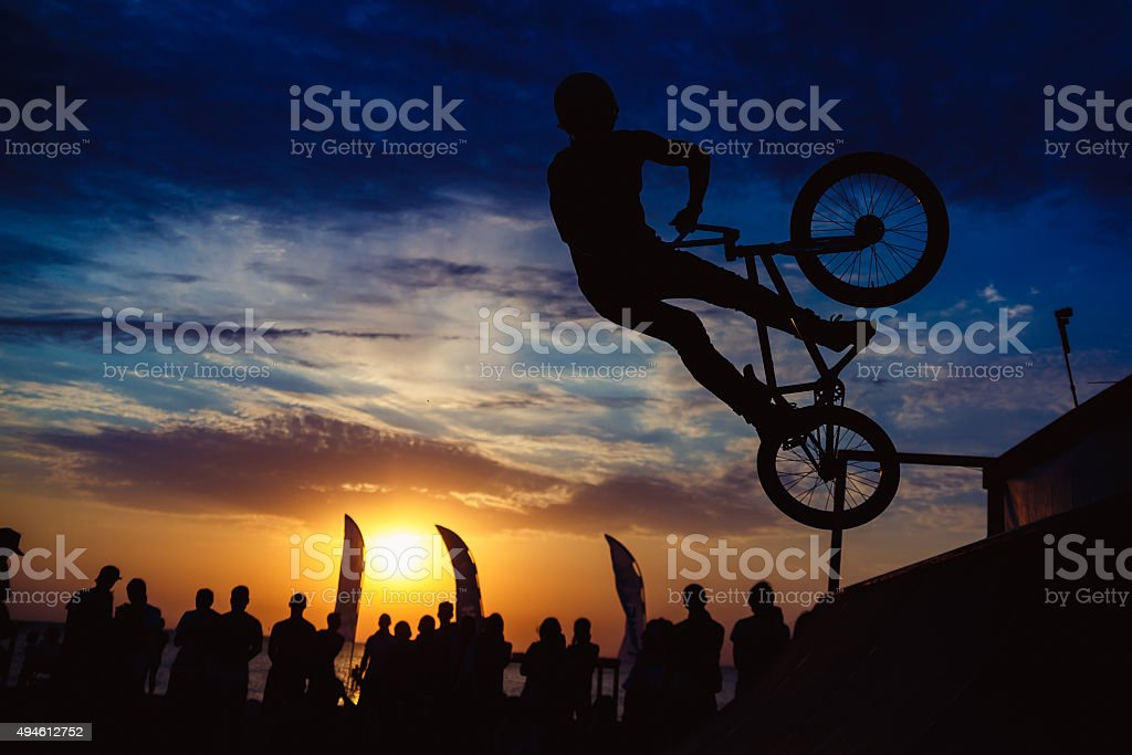 Silhouette of man doing extreme jump with bike stock photo