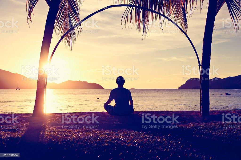 Silhouette of man doing yoga at sunset beach stock photo