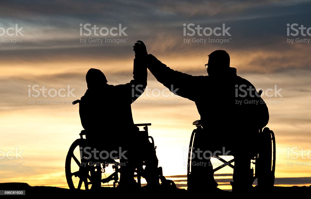 Silhouette of Man Encouraging Handicapped Boy in Wheelchair stock photo