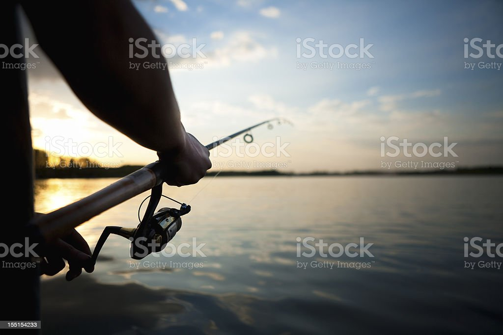 Silhouette of man fishing at night stock photo