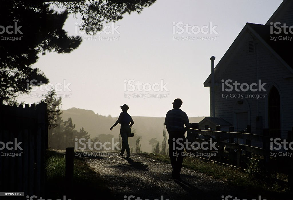 Silhouette of man following woman down a dark country lane stock photo