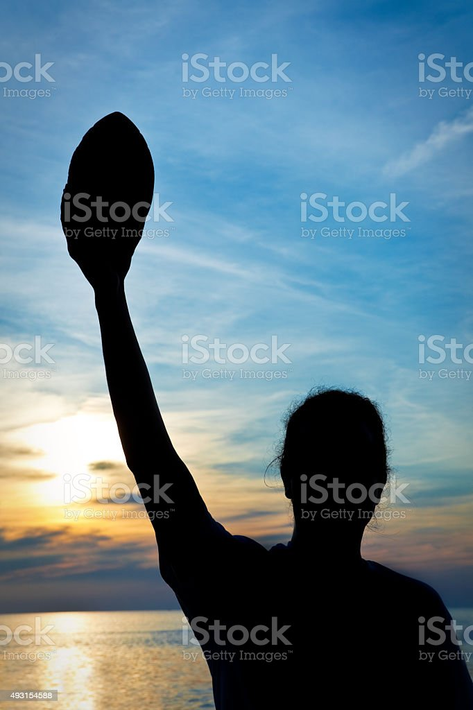 Silhouette Of Man Holding Football On Beach At Sunset stock photo