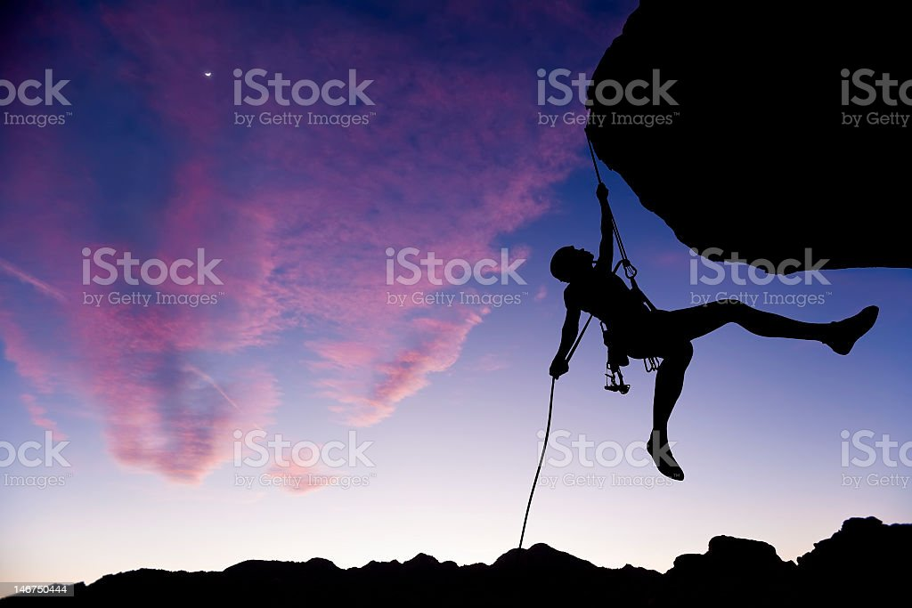Silhouette of man holding onto a rope from a rock stock photo