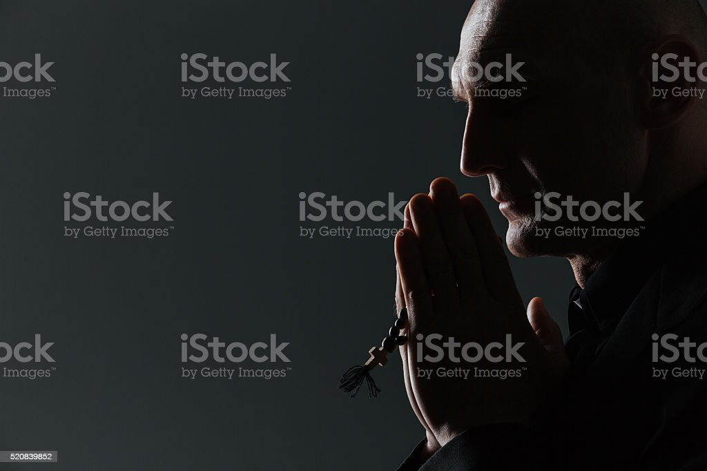 Silhouette of man holding rosary and praying stock photo