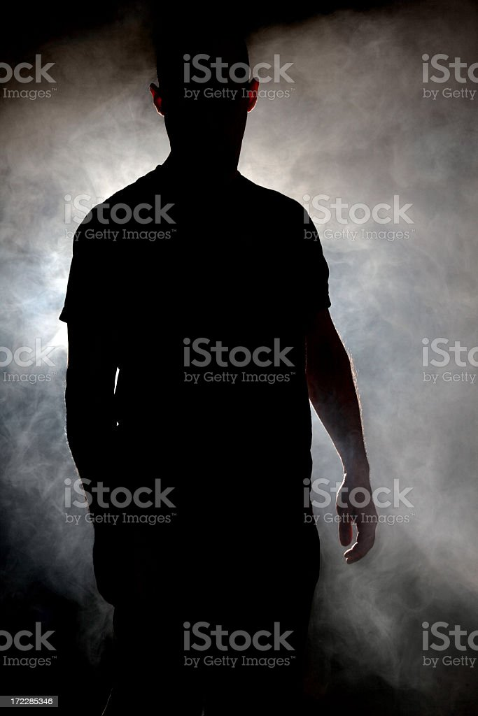 Silhouette of man in a cloud of smoke stock photo