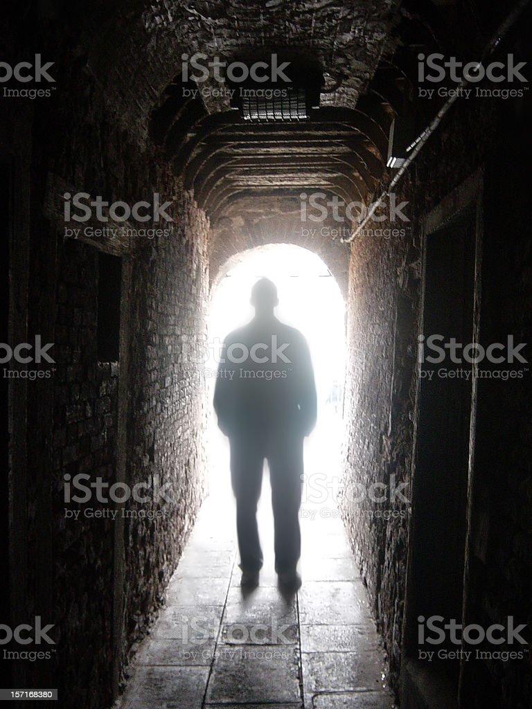 Silhouette d'un homme en noir avec la lumière au bout du Tunnel photo libre de droits