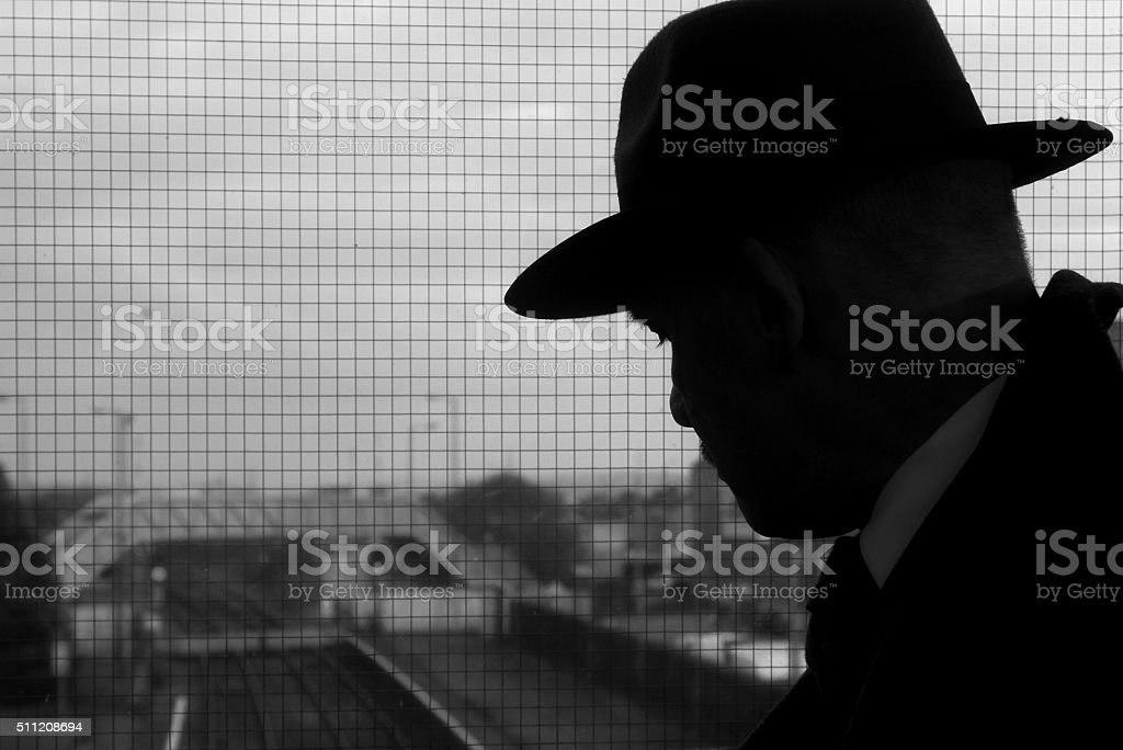 silhouette of man in fedora hat stock photo