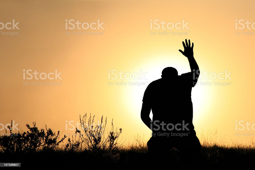 Silhouette of Man In Praise and Worship stock photo