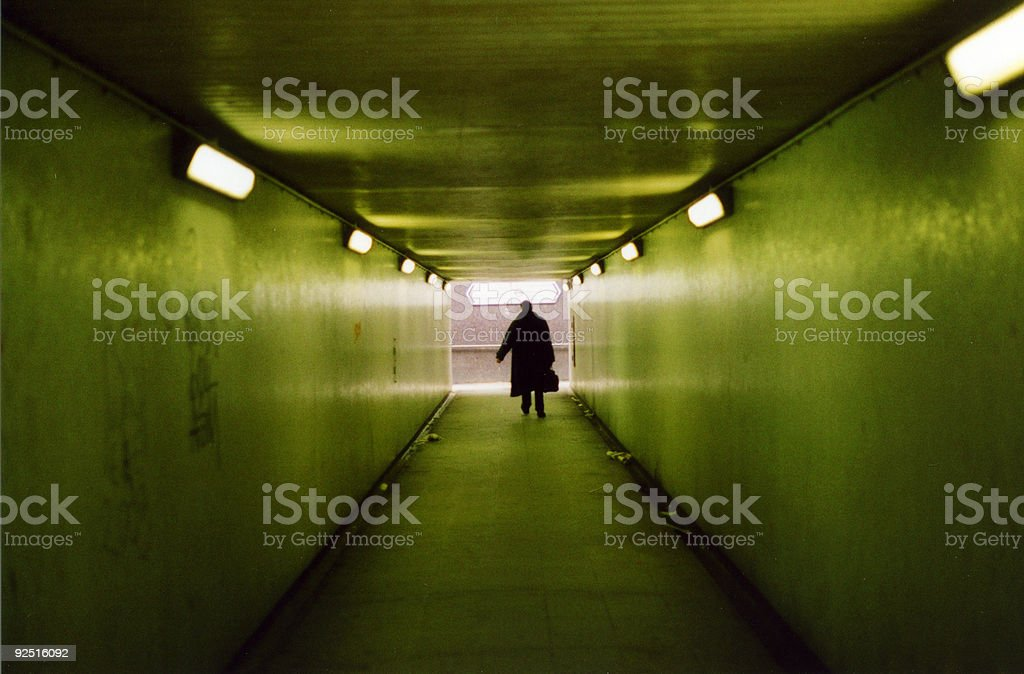 Silhouette of man in underpass with greenish light royalty-free stock photo