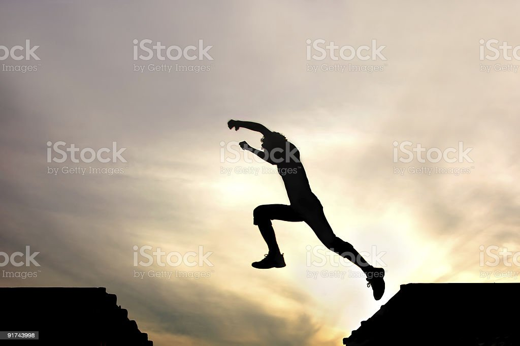 Silhouette of man jumping from roof to roof stock photo