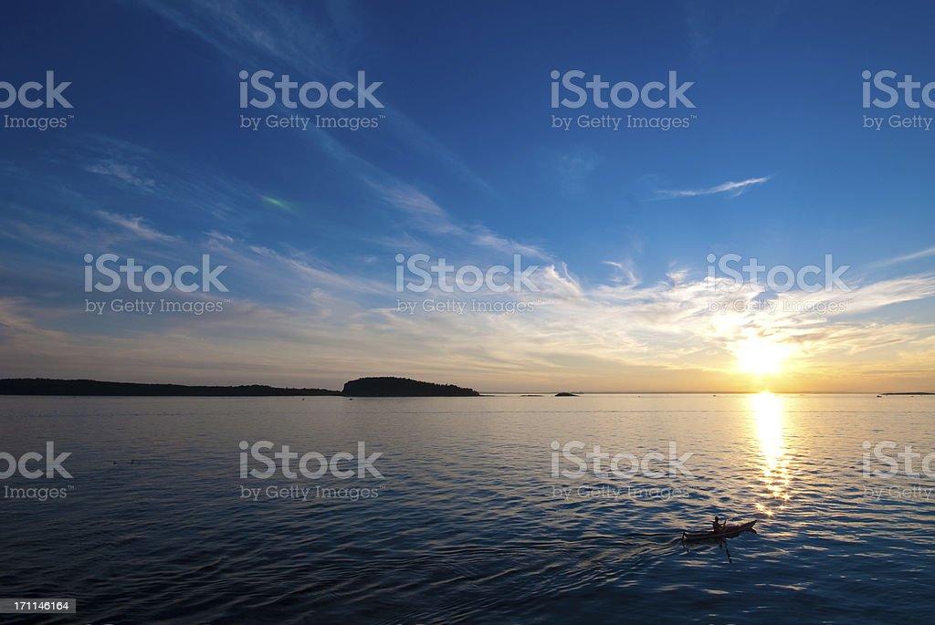 Silhouette of man kayaking at sunset royalty-free stock photo