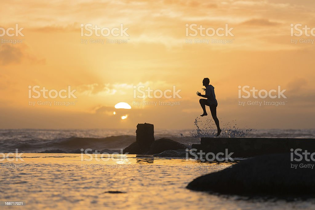 Silhouette of Man Leaping Off Sea Wall at Sunset royalty-free stock photo