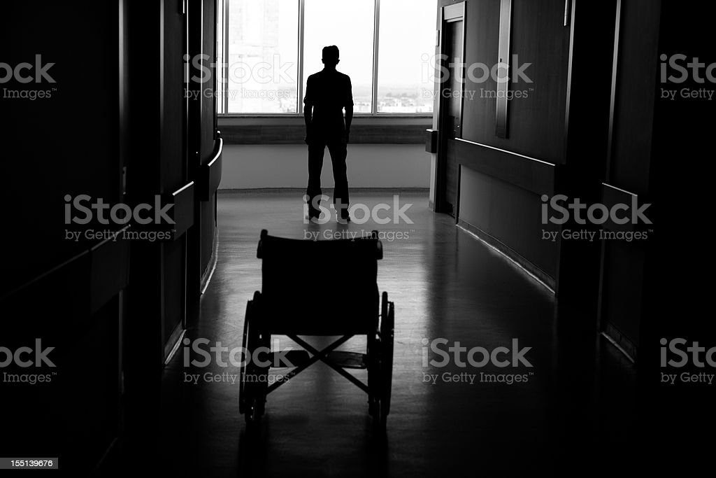 Silhouette of man leaving wheelchair in corridor of hospital royalty-free stock photo