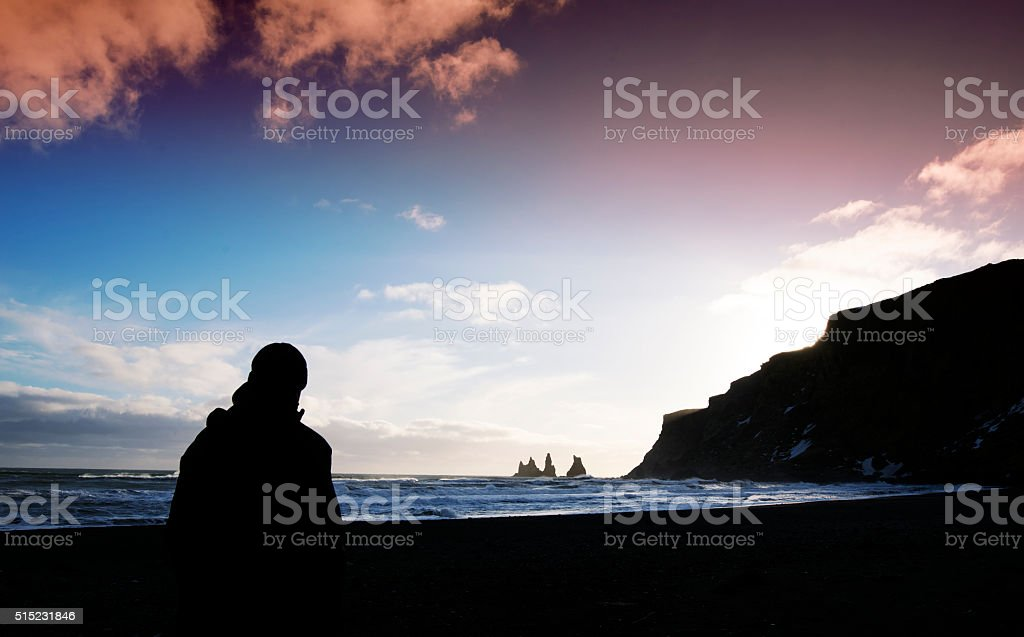 Silhouette of man  looking at  Reynisdrangar  sea stacks , Vik,Iceland stock photo