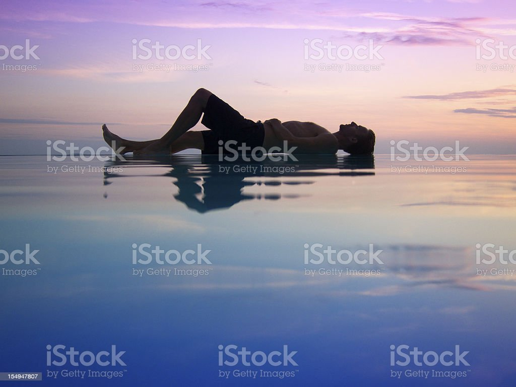 Silhouette of Man Lying Across Sunset Infinity Pool royalty-free stock photo