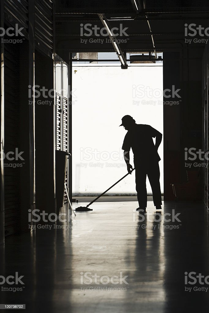 Silhouette of man moping floor stock photo