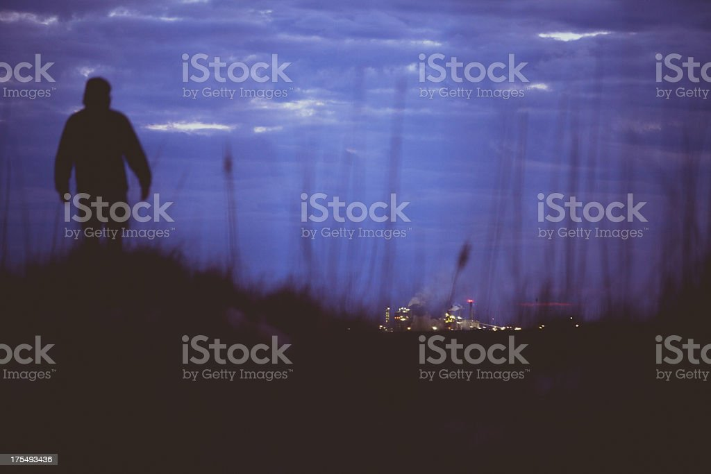 Silhouette of man observing city skyline from afar royalty-free stock photo