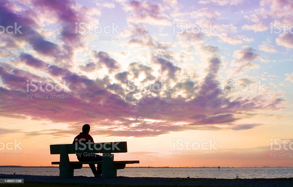 silhouette of man on bench watching sunset royalty-free stock photo