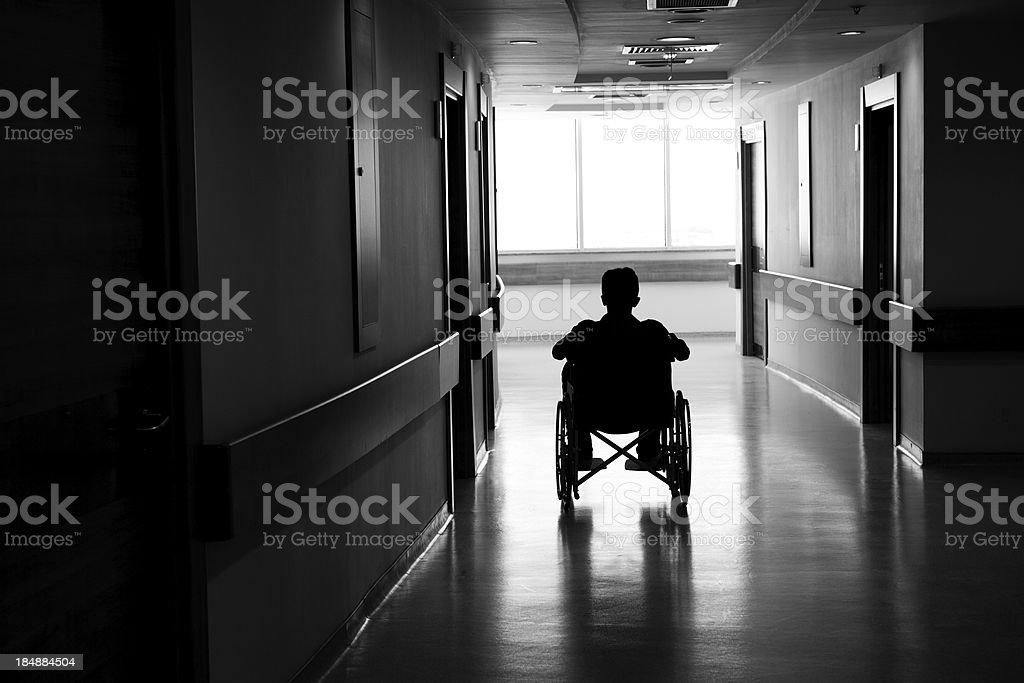 Silhouette of man on wheelchair in dark corridor stock photo