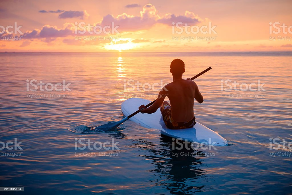 Silhouette of man paddleboarding at sunset stock photo