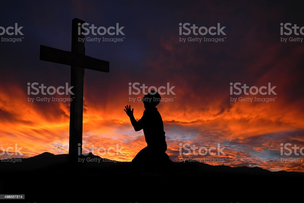 Silhouette of man praying to a cross with heavenly cloudscape stock photo