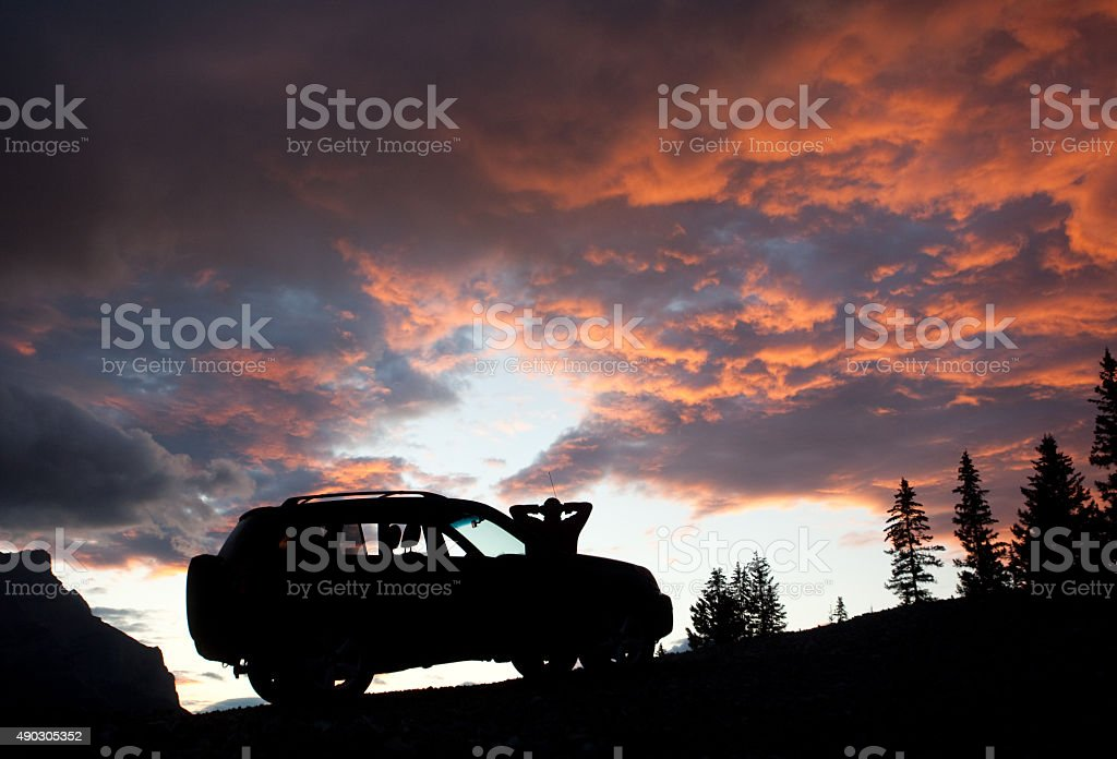Silhouette of Man Relaxing by SUV in the Mountains stock photo