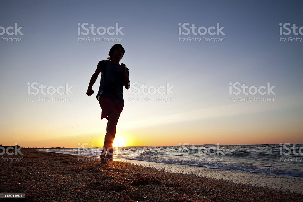 Silhouette of man running at beach beautiful summer sunset royalty-free stock photo