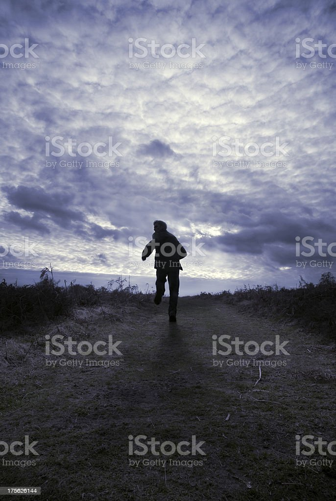 Silhouette of man running in field. stock photo