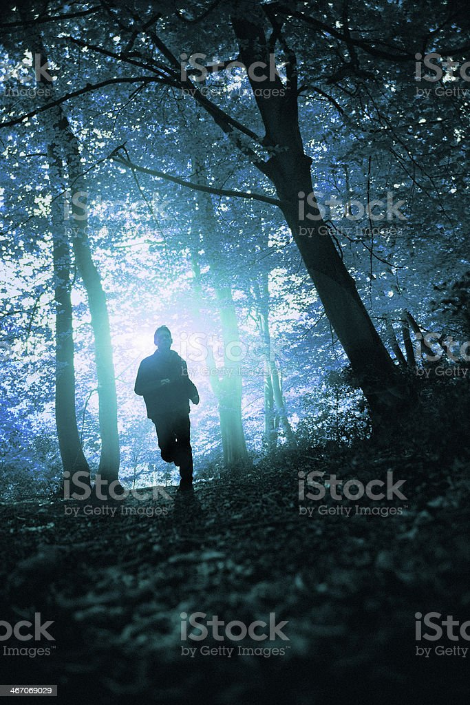 Silhouette of man running in forest. 2 stock photo