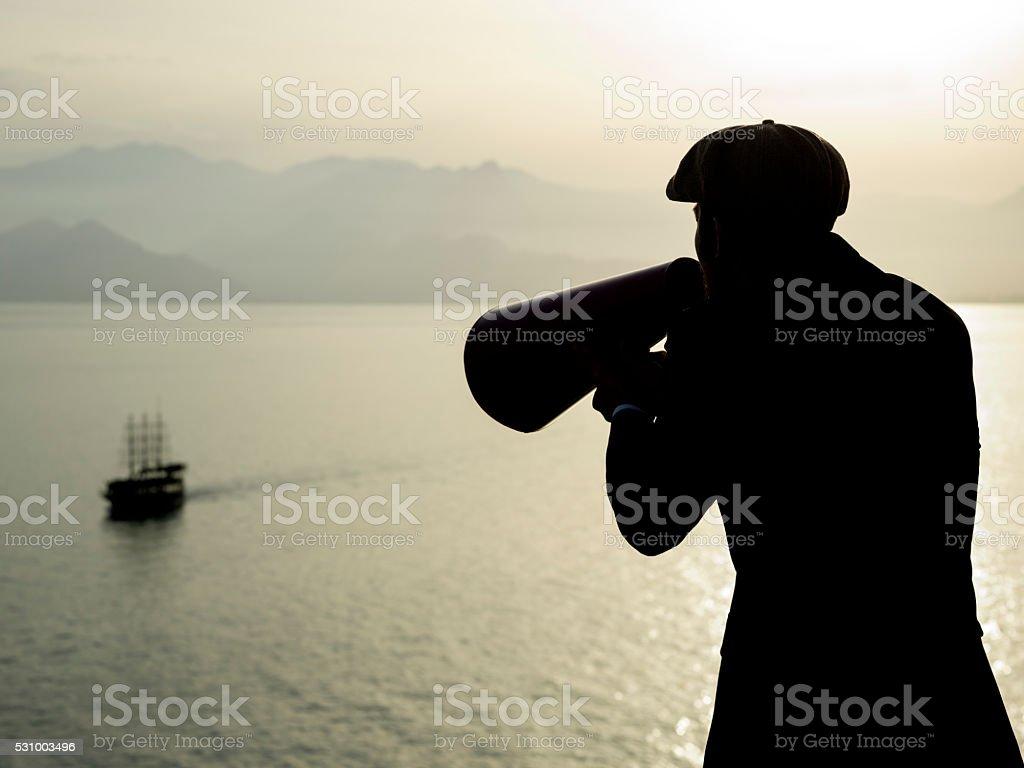 Silhouette Of Man Shouting Trough Megaphone Toward Sailing Ship stock photo
