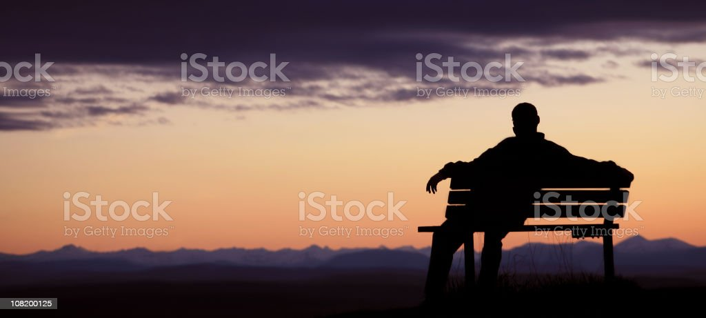 Silhouette of Man Sitting on bench at dusk royalty-free stock photo